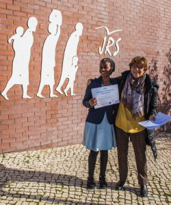 A migrant woman receives a certificate of a Portuguese language class from JRS Portugal academy